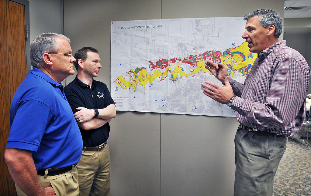 . Wichita Falls, Texas Public Works Director Russell Schreiber, right, talks with Mayor Glenn Barham, left, and City Manager Darron Leiker, Monday, May 25, 2015, at the Emergency Operations Center about local flooding concerns and what is being done in affected areas of town. In the U.S., the weather system dumped record rainfall on parts of the Plains and Midwest, spawning tornadoes and causing major flooding that forced at least 2,000 Texans from their homes. (Torin Halsey/Times Record News via AP)