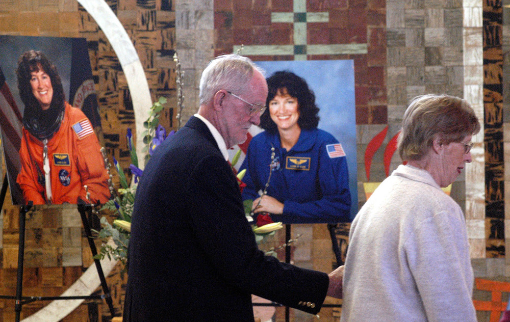 . Robert Salton, and his wife Harriet, make their way to their seats prior to a memorial service for his daughter, space shuttle Columbia astronaut Laurel Clark, at the First Unitarian Church in Albuquerque, N.M., Saturday, Feb. 22, 2003. Clark lived in Albuquerque for a brief period when she was a child. (AP Photo/Jake Schoellkopf)