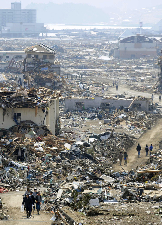 . People walk amid the rubble in Rikuzentakata, Iwate prefecture, northern Japan, Sunday, March 13, 2011, two days after the powerful earthquake-triggered tsunami hit the country\'s east coast. (AP Photo/Kyodo News)