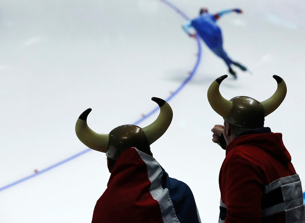 . Two fans dressed as Vikings and draped in the Norwegian national flag watch of Henrik Fagerli Rukke of Norway, rear, compete during the men\'s 1,000 meters speedskating race at the Gangneung Oval at the 2018 Winter Olympics in Gangneung, South Korea, Friday, Feb. 23, 2018. (AP Photo/John Locher)