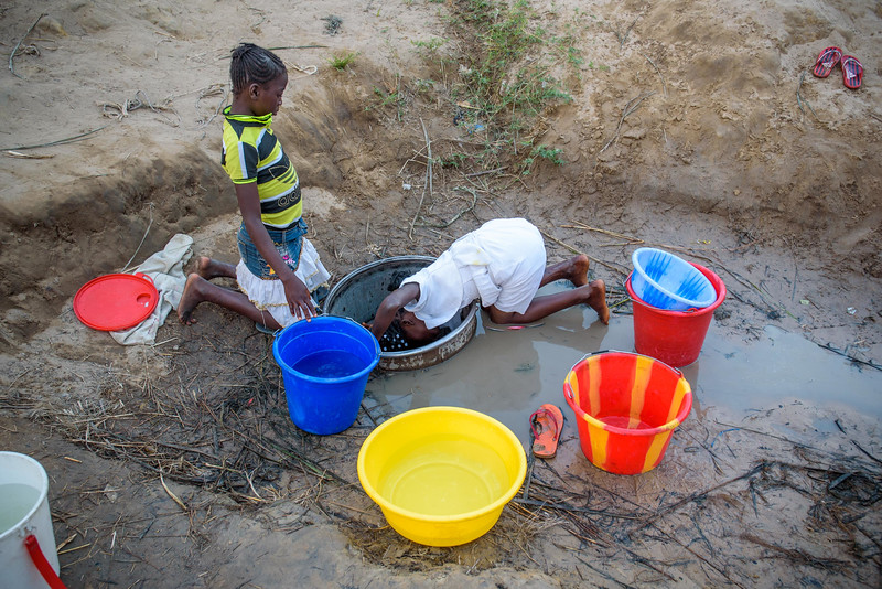 """Kapinga Alphoncine, 13 yr-old girl (white dress) makes the long journey to collect water with her best friend, Vicky (yellow and black striped shirt).  She lives with her grandmother, Kapinga Godelive, 66 and her 3 brothers: 1-Francois Ngondo, 14 2-Mbuyamba Phillip, 9 3-Beya Honore, 6 Kananga, DRC Democratic Republic of Congo.  Water Kapinga walks to the stream to get water, often with her best friend, Ngalula Vicky, 12 (just call her Vicky.) The girls walk a winding path for about a three-quarters of a mile to a river that is divided into a series of ponds. In the center, people dip into shallow wells to fill their containers. The girls enjoy their trips together. They sometimes make as many as 4 or 5 day.  They agree that all the water from the first series of trips will go to one family, then the next will go to the other. """"I am taking an hour to get water. It is very heavy, especially when I put it on my head.""""  Inside Kapinga's four-room house the walls are paint splattered. There is little furniture except for two small tables and an old cabinet. On top sits a dusty old television. A peek behind reveals that it has no cord. Kapinga sits on a low, wooden bench against one wall reading an old school exercise book of English lessons. """"Good morning my friends, good morning.""""  Her English is good in spite of a mispronunciation here and there. High up on the wall to the right is a crucifix. It's as battle worn as the rest of the house. Light streams in through the numerous holes in the tin-sheeted roof. In the yard outside, the house is ringed on all sides with gardens of potato and cassava leaves, sorrel and sugarcane among other things.  In one corner of the yard a few visitors gather on homemade chairs under a thatched-roof patio. Across the compound the afternoon sun throws light on the smaller of the two buildings there. In chalk, just below the roof line are the words, """"Il n'ya pas de rose sans epines."""" There is no rose without thorns.  Home Life Her family is"""