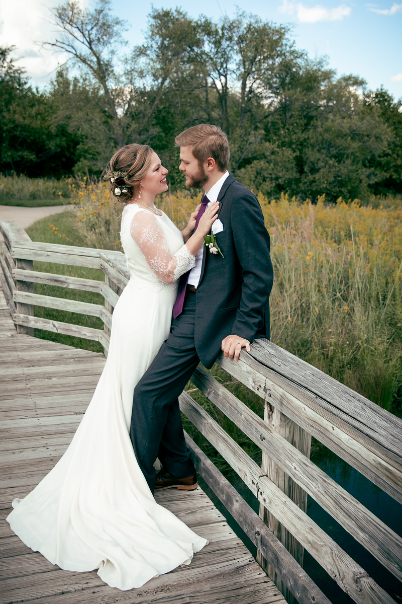 A bride and groom smiling at one another while standing on a bridge next to a field and woods