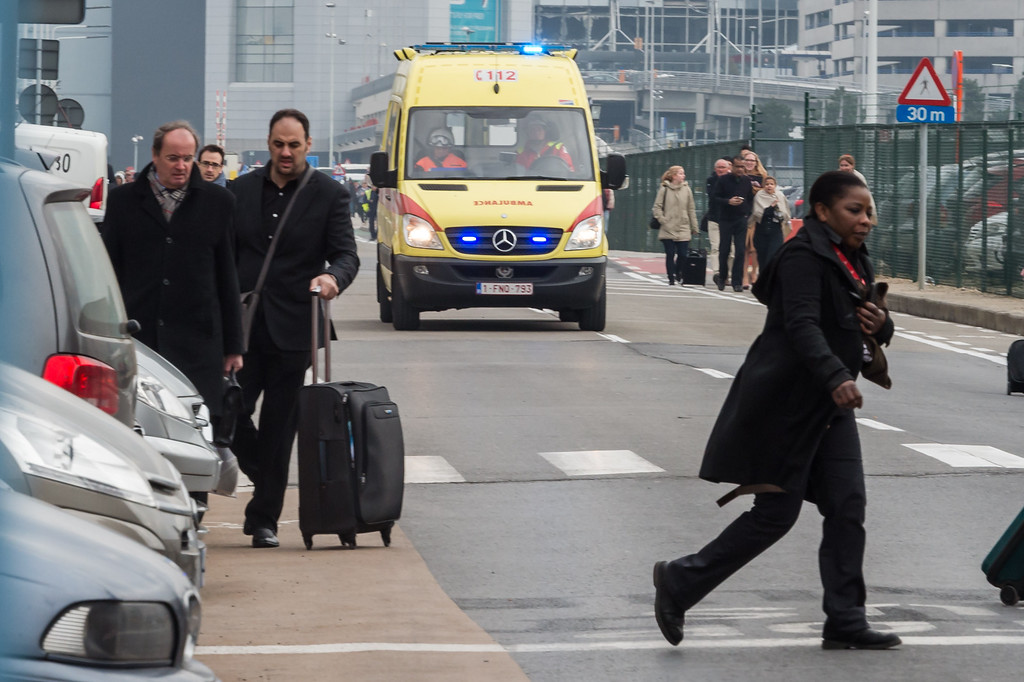 . Ambulances arrive to the scene at Brussels airport, after explosions rocked the facility in Brussels, Belgium, Tuesday March 22, 2016. Authorities locked down the Belgian capital on Tuesday after explosions rocked the Brussels airport and subway system, killing at least 13 people and injuring many more. Belgium raised its terror alert to its highest level, diverting arriving planes and trains and ordering people to stay where they were. Airports across Europe tightened security. (AP Photo/Geert Vanden Wijngaert)