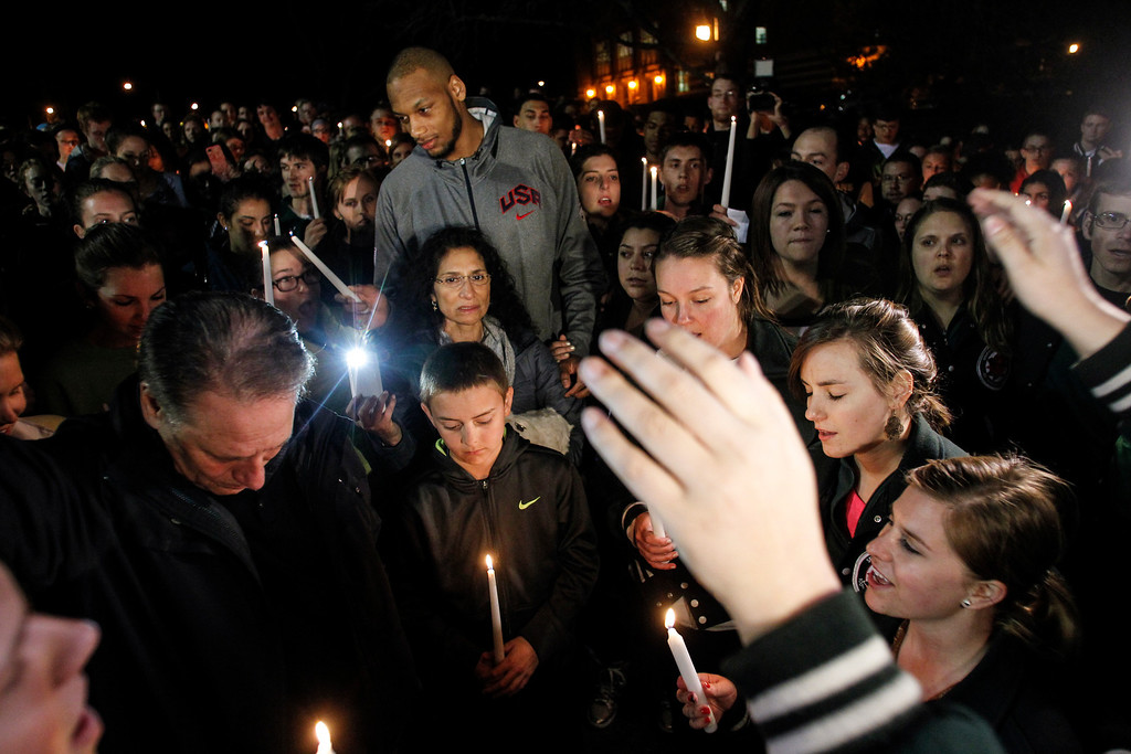 ". People, including MSU Head Basketball coach Tom Izzo, second from left, his son Steven, next to Izzo, his wife Lupe, middle, and MSU senior center Adreian Payne, behind Lupe,  attend a candelight vigil in front of ""the Rock\"" along the banks of the Red Cedar river on the campus of Michigan State University, Wednesday evening, March 9, 2014, in Lansing, Mich., to honor the legacy of \""Princess Lacey\"" Holsworth.  The 8-year-old Hosworth lost her battle with cancer Tuesday evening  which has been nationally publicized due to her close relationship with her \""adopted big brother,\"" MSU senior center Adreian Payne, the MSU men\'s basketball team, and the Spartan community.   (AP Photo/The State Journal, Matthew Dae Smith)  NO SALES"