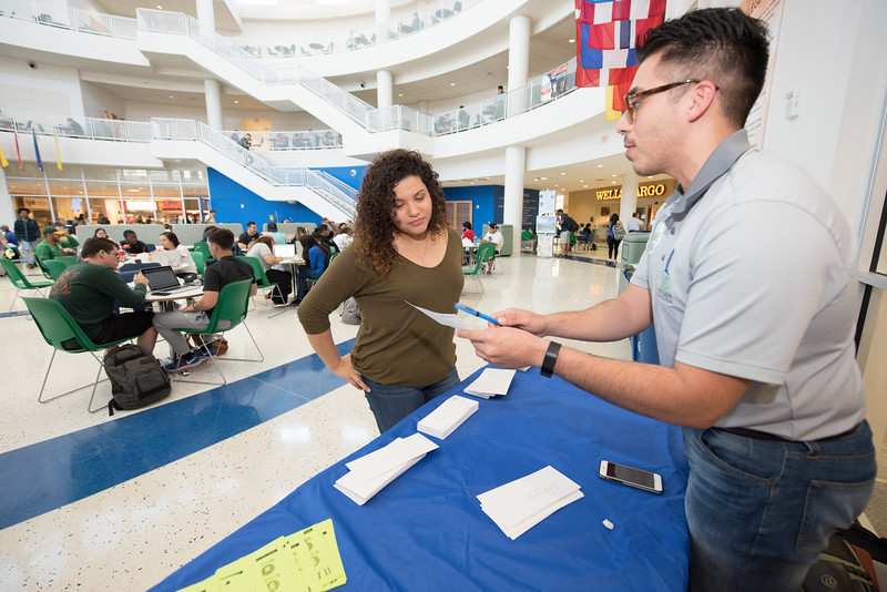 Frank Garcia (right) goes over the process of filling out a donor pledge card with student Zoe Rodriguez during the Go Blue Give Green campaign.