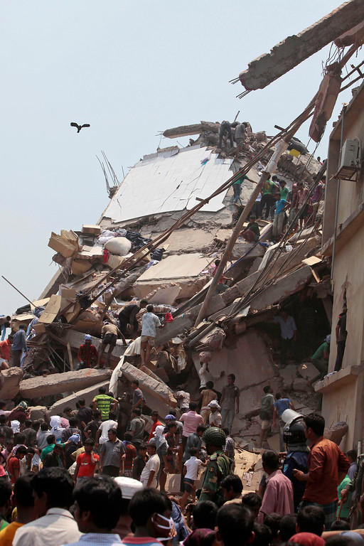 . Rescue workers and people look for survivors after an eight-story building housing several garment factories collapsed in Savar, near Dhaka, Bangladesh, Wednesday, April 24, 2013. (AP Photo/ A.M. Ahad)