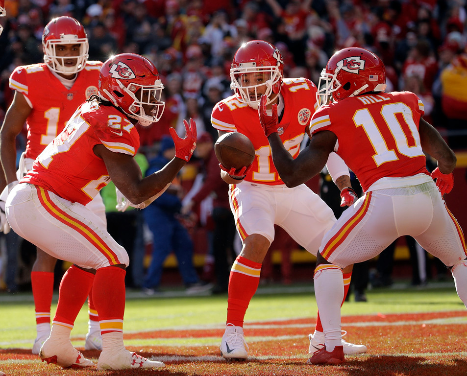 . Kansas City Chiefs running back Kareem Hunt (27) celebrates his touchdown against the Oakland Raiders with teammates wide receiver Tyreek Hill (10) and wide receiver Albert Wilson (12) during the first half of an NFL football game in Kansas City, Mo., Sunday, Dec. 10, 2017. (AP Photo/Charlie Riedel)