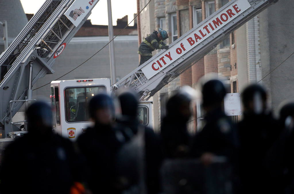 . A firefighter works as police stand guard during a protest, Monday, April 27, 2015, following the funeral of Freddie Gray in Baltimore. (AP Photo/Matt Rourke)