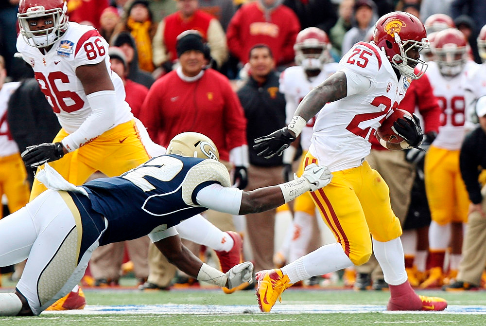 Description of . Southern California running back Silas Redd (25) rushes past Georgia Tech linebacker Jabari Hunt-Days during the Sun Bowl NCAA college football game, Monday, Dec. 31, 2012, in El Paso, Texas. (AP Photo/Mark Lambie)