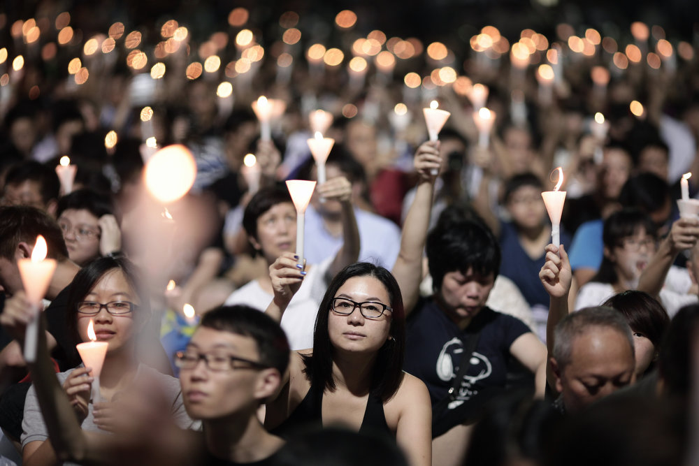 . People take part in a candlelight vigil held to mark the 24th anniversary of the 1989 crackdown at Tiananmen Square, in Hong Kong, on June 4, 2013. More than 100,000 people were expected to attend the candlelight vigil in the former British colony which is the only place in China where the brutal military intervention that ended weeks of nationwide democracy protests in 1989 is openly commemorated.   ANTHONY WALLACE/AFP/Getty Images