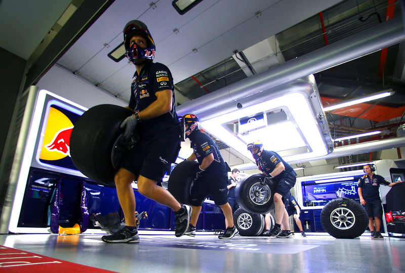. Member of the Infiniti Red Bull Racing run tires out of the garage to the pit lane as they take part in a pit stop practice session during previews ahead of the Singapore Formula One Grand Prix at Marina Bay Street Circuit on September 18, 2014 in Singapore, Singapore.  (Photo by Mark Thompson/Getty Images)
