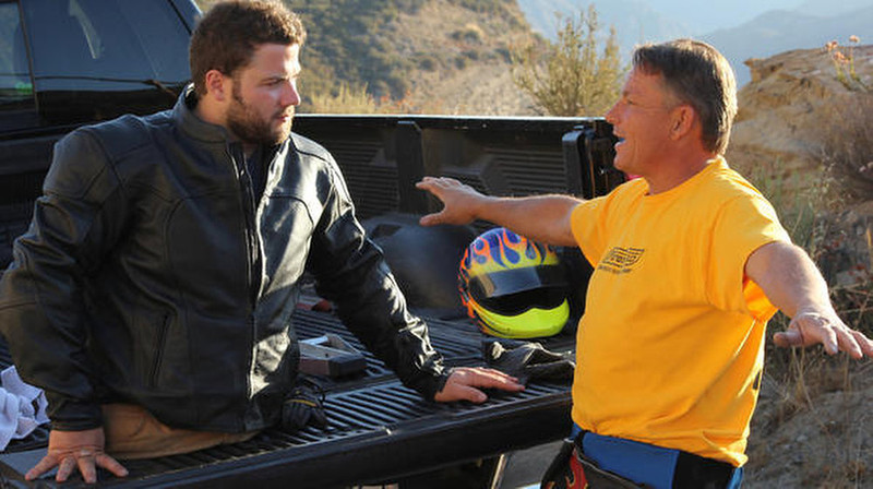 . Kevin gets some advice on how to balance on the luge before hitting the streets of LA for a downhill race.