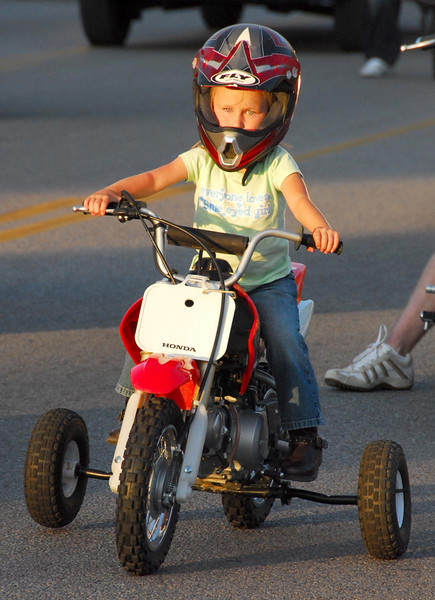 6/9/07 – The Orem Fest parade is how we kick off every summer. This year there was a group of motorcycles, big Harleys, touring bikes, bullet bikes and even ATVs, bringing up the tail end of the parade. This little girl was riding along with her dad on her motorbike with training wheels. She stole all the attention she was so cute.
