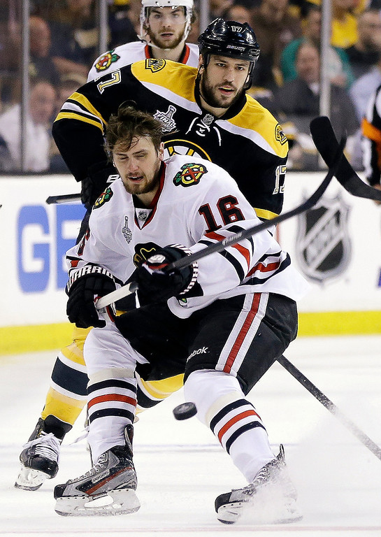 . Chicago Blackhawks center Marcus Kruger (16) moves the puck in front of Boston Bruins left wing Milan Lucic, rear, during the first period in Game 3 of the NHL hockey Stanley Cup Finals in Boston, Monday, June 17, 2013. (AP Photo/Elise Amendola)