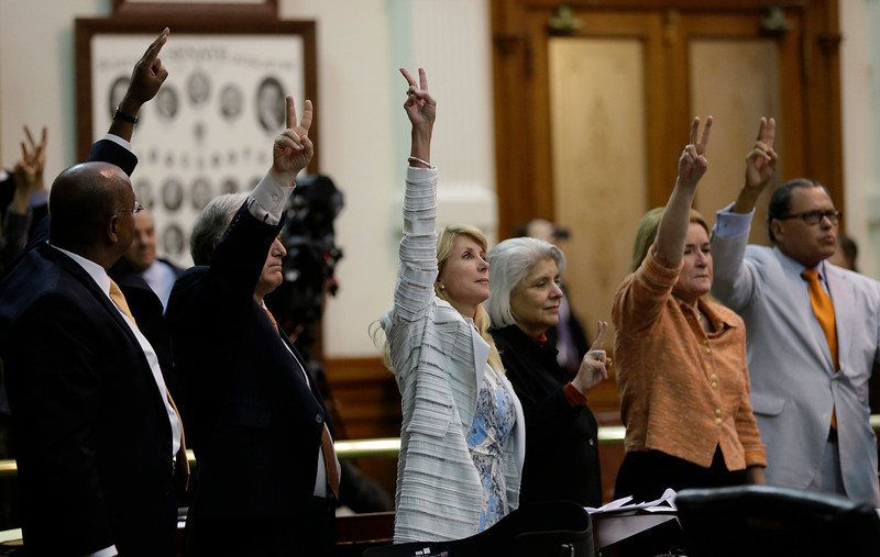 . Sen. Wendy Davis, D-Fort Worth, center, who tries to  filibuster an abortion bill, hold up a no vote as time expires, Wednesday, June 26, 2013, in Austin, Texas. Amid the deafening roar of abortion rights supporters, Texas Republicans huddled around the Senate podium to pass new abortion restrictions, but whether the vote was cast before or after midnight is in dispute. If signed into law, the measures would close almost every abortion clinic in Texas.  (AP Photo/Eric Gay)