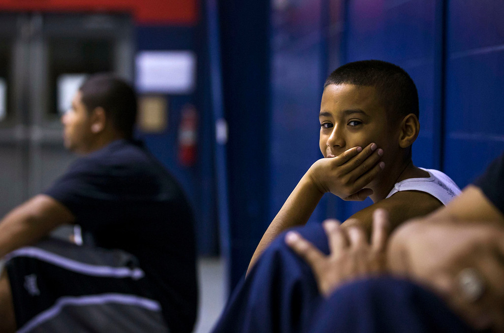 . Downey Christian high school varsity basketball player 11-year-old Julian Newman (L) watches Friday evening pickup basketball games at Downey Christian School in Orlando, Florida February 22, 2013. At 4 feet 5 inches tall, starting point guard Julian Newman stands waist high next to other players on his Florida high school basketball team. But his talent towers over the competition. At only 11, Newman leads the state of Florida in assists per game this season and ranks fifth nationally, according to Maxpreps.com, which maintains statistics on high school sports.  REUTERS/Scott Audette
