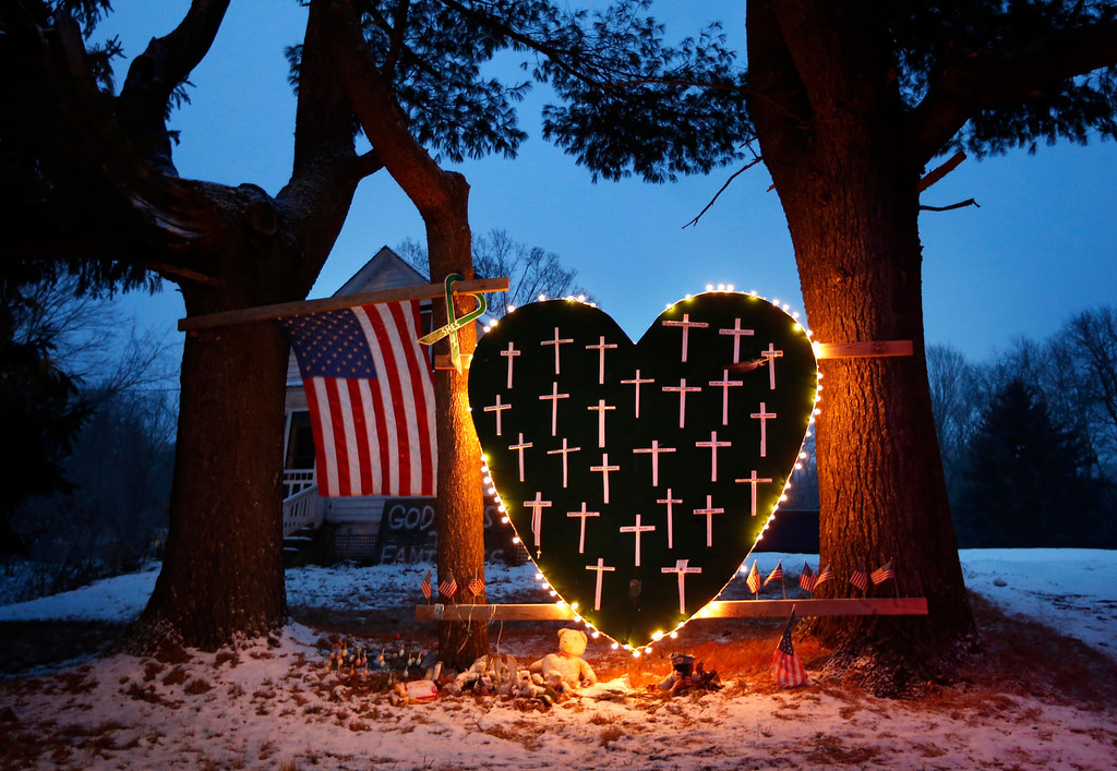 . A makeshift memorial with crosses for the victims of the Sandy Hook massacre stands outside a home in Newtown, Conn., Saturday, Dec. 14, 2013, the one-year anniversary of the shootings.  (AP Photo/Robert F. Bukaty)