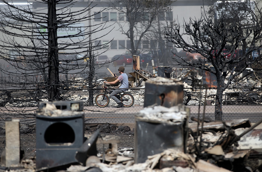 . A cyclist stops to take a picture of the remains of destroyed homes on September 16, 2014 in Weed, California. A fast moving wildfire fueled by high winds ripped through the town of Weed on the afternoon of September 15, burning 100 structures including the high school and lumber mill.  (Photo by Justin Sullivan/Getty Images)