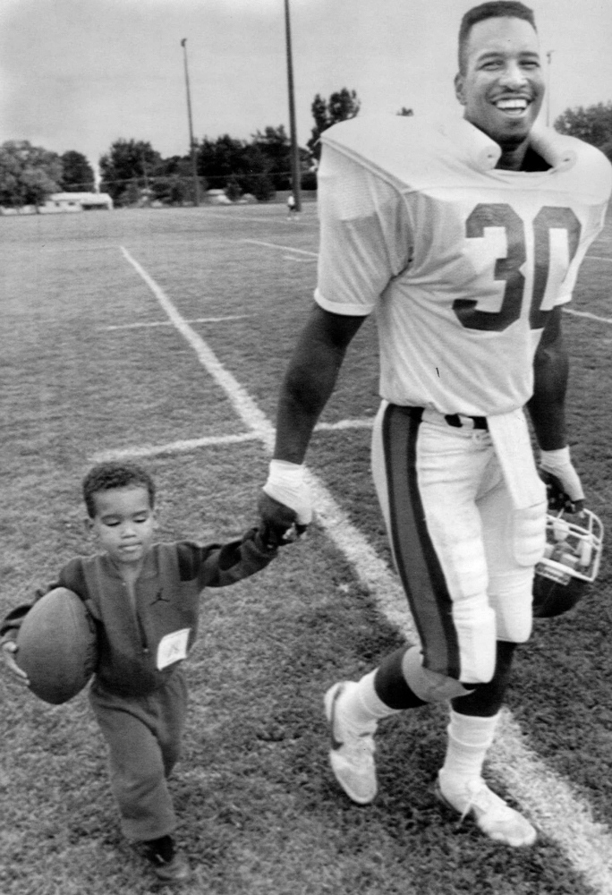 . Aug. 1, 1981: Running back Steve Sewell walked off the field with his 3-year-old son Samuel at the end of practice (The Denver Post)