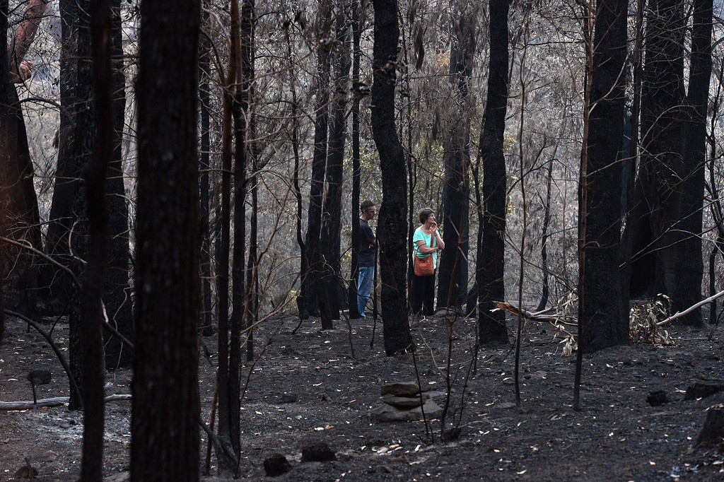 . Jennifer Schweinsberg walks with her son David in the backyard of her burnt house at Winmalee in the Blue Mountains on October 22, 2013. Jennifer visited her gutted house for the first time after spending four days in the hospital due to chest pain after seeing her burning house; she lost her property in the bushfire where she spend 40 years of her life with her two children.     AFP PHOTO/  Saeed KHAN/AFP/Getty Images