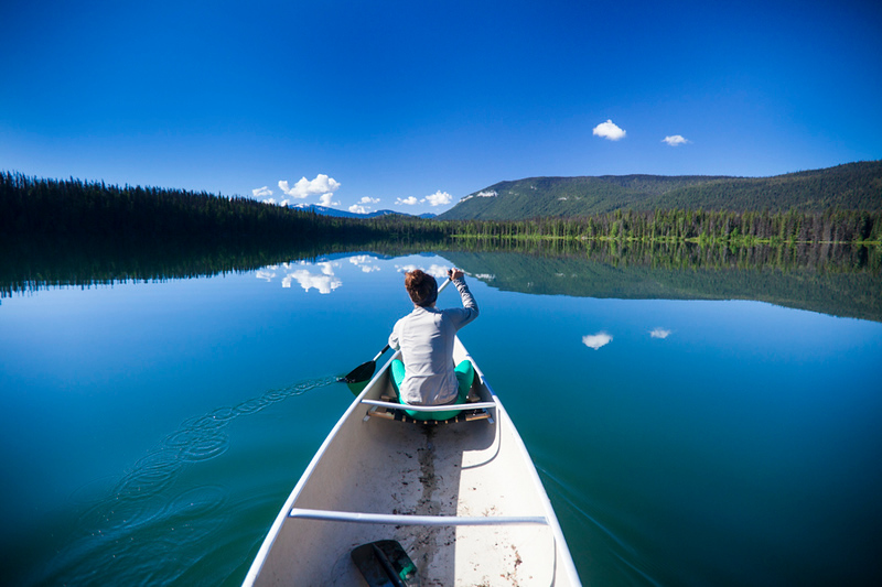 Canoeing across Unna Lake in Bowron Lake Provincial Park.