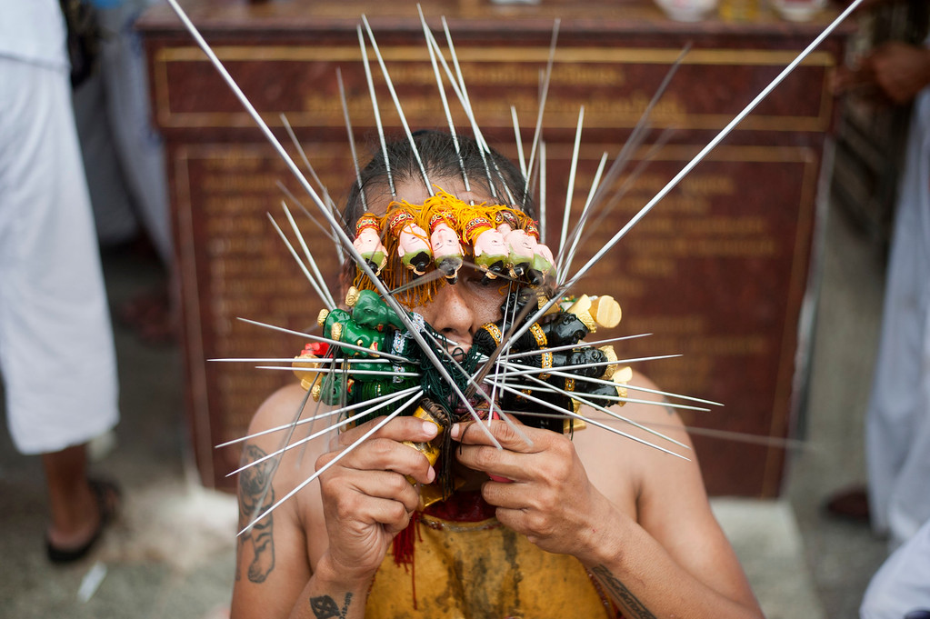 . A vegetarian festival devotee prepares himself to get off the needles of his face after a parade through the downtown streets at Jui Tui shrine on September 30, 2014 in Phuket, Thailand. (Photo by Borja Sanchez-Trillo/Getty Images)