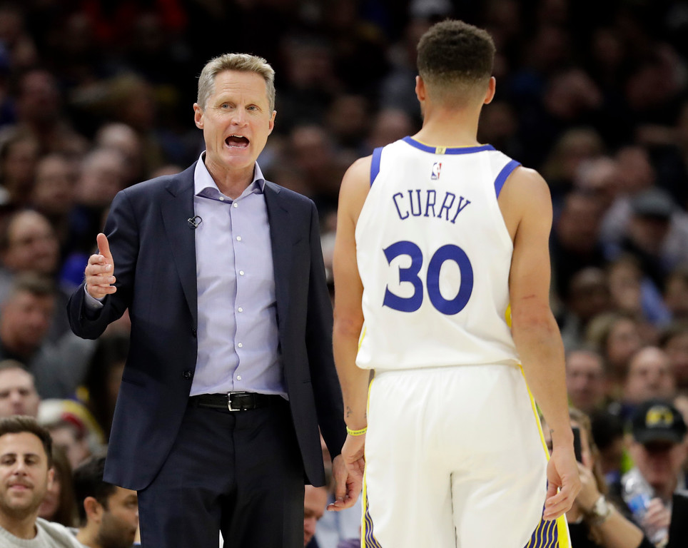 . Golden State Warriors head coach Steve Kerr, left, talks with Stephen Curry in the second half of an NBA basketball game against the Cleveland Cavaliers, Monday, Jan. 15, 2018, in Cleveland. (AP Photo/Tony Dejak)