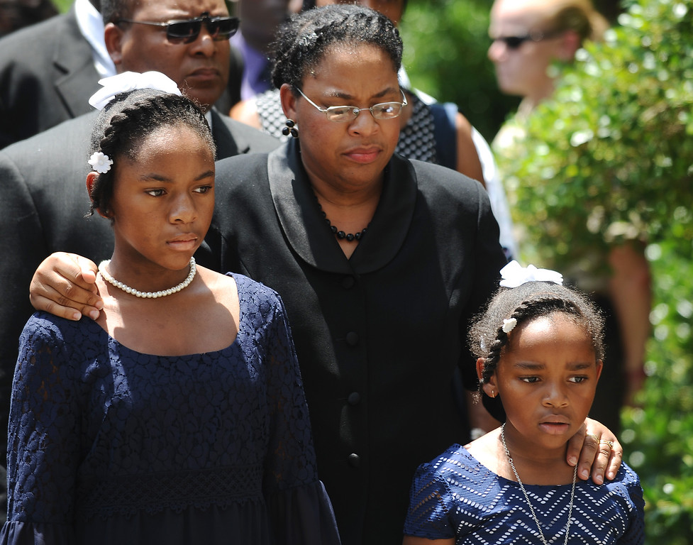 . Sen. Clementa Pinckney\'s wife Jennifer Pinckney, center, and her daughters, Eliana, left, and Malana, right, follow his casket into the South Carolina Statehouse, Wednesday, June 24, 2015, in Columbia, S.C. Pinckney\'s open coffin was being put on display under the dome where he served the state for nearly 20 years. Pinckney was one of those killed in a mass shooting at the Emanuel AME Church in Charleston. (AP Photo/Rainier Ehrhardt)