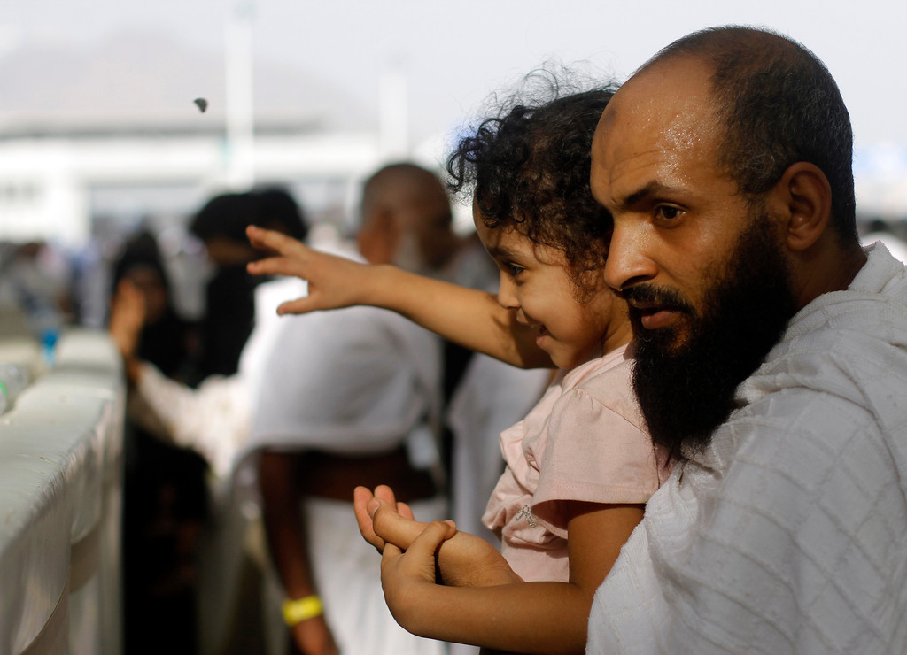""". A Muslim pilgrim carries his child as they cast stones at a pillar, symbolizing the stoning of Satan, in a ritual called \""""Jamarat,\"""" the last rite of the annual hajj, in the Mina neighborhood of Mecca, Saudi Arabia, Tuesday, Oct. 15, 2013. (AP Photo/Amr Nabil)"""
