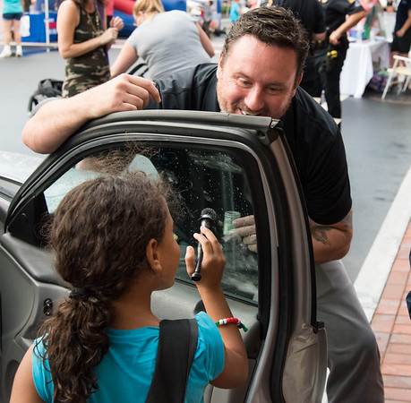 08/07/18 Wesley Bunnell | Staff New Britain Police held their annual National Night Out 2018 on Tuesday evening in a blocked off Central Park area. Yeralis Velez, age 7, dusts for fingerprints on a police vehicle with the help of Det. Brian Shea.