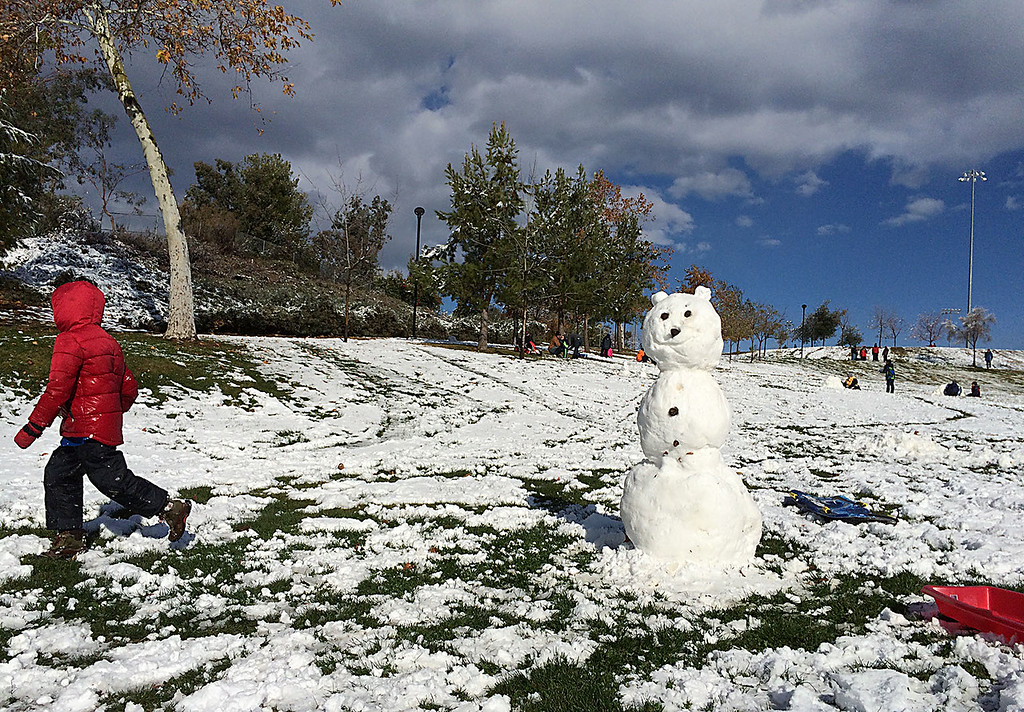 . Jonathan Valdez, 11, and the rest of his Yucapia family built two snowmen Wednesday morning. One at their home and the other, here in Yucaipa Community Park. Residents of Yucaipa, Calif., awoke Wednesday December 31, 2014 to a blanket of snow left behind by Tuesday\'s winter storm with weather reports claiming three to five inches of snow. (Staff photo by Rick Sforza/The Sun)
