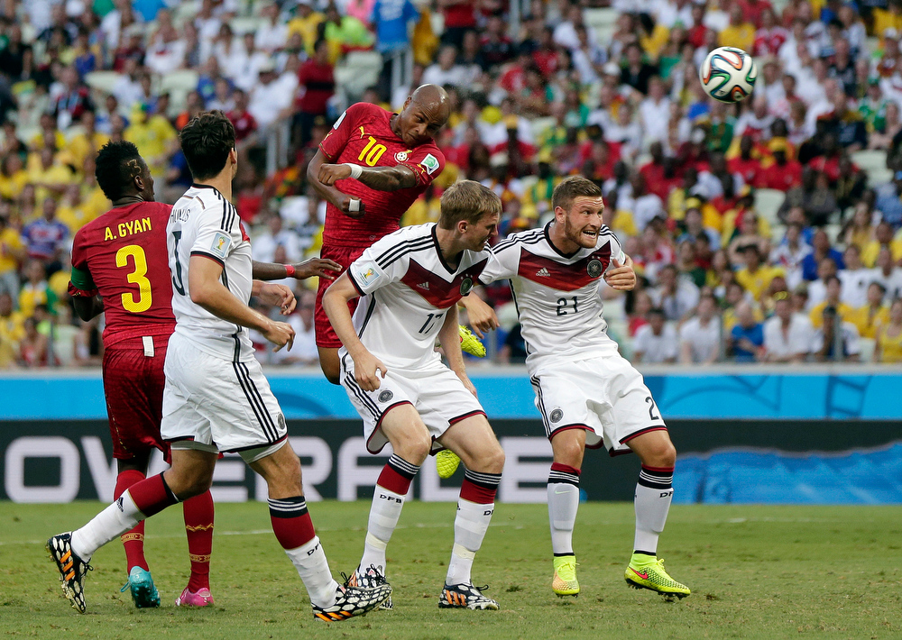 . Ghana\'s Andre Ayew heads the ball over Germany\'s Per Mertesacker, center, and Germany\'s Shkodran Mustafi, right, to score his sides\' first goal during the group G World Cup soccer match between Germany and Ghana at the Arena Castelao in Fortaleza, Brazil, Saturday, June 21, 2014. (AP Photo/Marcio Jose Sanchez)