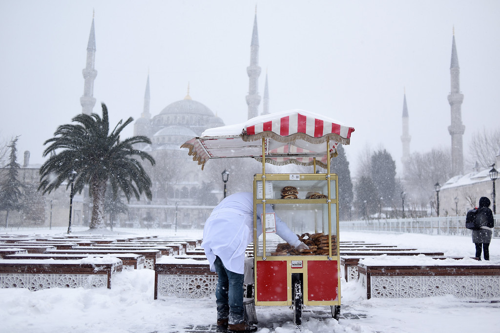 . A vendor selling traditional Turkish simit (bread) waits for customers during snowfall in the historic Sultanahmet district in Istanbul, Saturday, Jan. 7, 2017. Heavy snow clogged roads, shipping traffic in Bosphorus and forced hundreds of flight cancellations in the Turkish metropolis. (Mert Akyol/Depo Photos via AP)