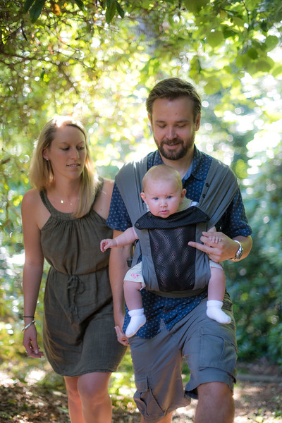 Izmi_Baby_Carrier_Breeze_Mid_Grey_Lifestyle_Front_Facing_Carry_Mum_And_Dad_Walking_In_Woods.jpg