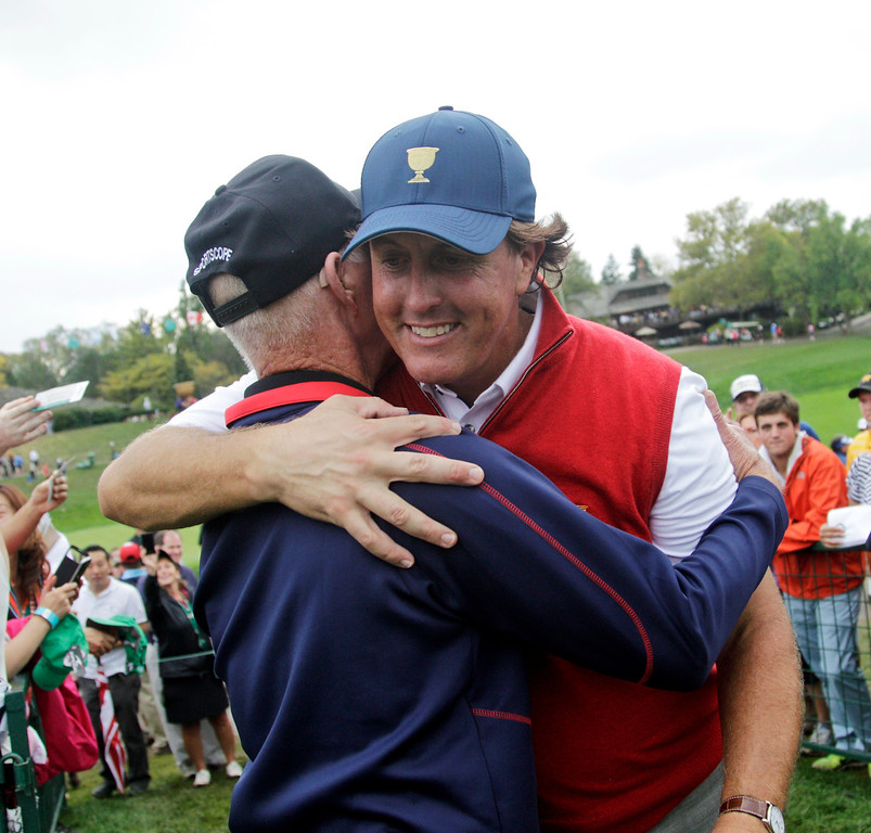 . United States team player Phil Mickelson, right, hugs his father Phil Mickelson Sr. after the U.S. won the Presidents Cup golf tournament at Muirfield Village Golf Club Sunday, Oct. 6, 2013, in Dublin, Ohio. (AP Photo/Jay LaPrete)