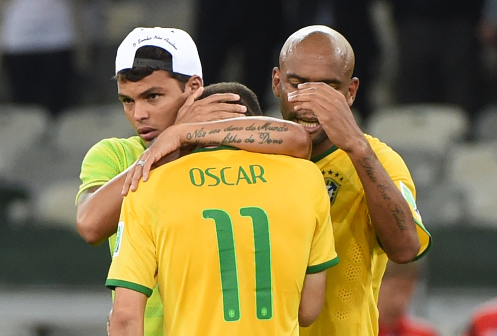 . Brazil\'s midfielder Oscar (C), Brazil\'s defender and captain Thiago Silva (L) and Brazil\'s defender Maicon  react after defeat in the semi-final football match between Brazil and Germany at The Mineirao Stadium in Belo Horizonte on July 8, 2014, during the 2014 FIFA World Cup . (PEDRO UGARTE/AFP/Getty Images)