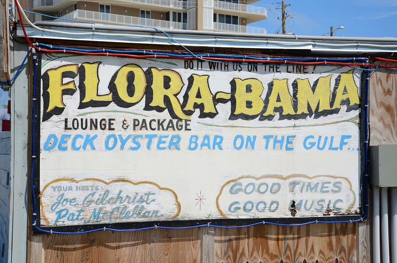 "The Flora-Bama Bar (aka The Bama ), located on Perdido Key in Pensacola, Florida, is a beachside oyster bar, beach bar, and Gulf Coast cultural landmark, touted as being America's ""Last Great Roadhouse"". The Flora-Bama takes its name from its location on the Florida-Alabama border line. The bar is in fact located all within Florida, with the Alabama line being about six feet from the western outside wall.  Once you enter this maze of bars and stages you can see that the term ""dive"" would be a compliment."