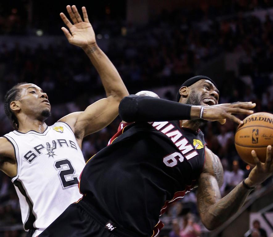 . Miami Heat forward LeBron James (6) struggles under the basket against San Antonio Spurs forward Kawhi Leonard (2) during the first half in Game 2 of the NBA basketball finals on Sunday, June 8, 2014, in San Antonio. (AP Photo/Eric Gay)