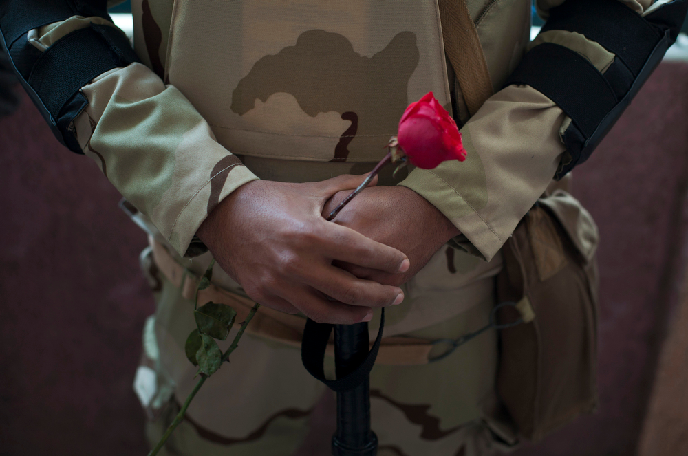 . An Egyptian army soldier holds a red rose as he stands guard a polling station during the vote in the country\'s constitutional referendum in Cairo, Egypt, Tuesday, Jan. 14, 2014. Upbeat and resentful of the Muslim Brotherhood, Egyptians voted Tuesday on a new constitution in a referendum that will pave the way for a likely presidential run by the nation\'s top general months after he ousted Islamist President Mohammed Morsi.(AP Photo/Khalil Hamra)
