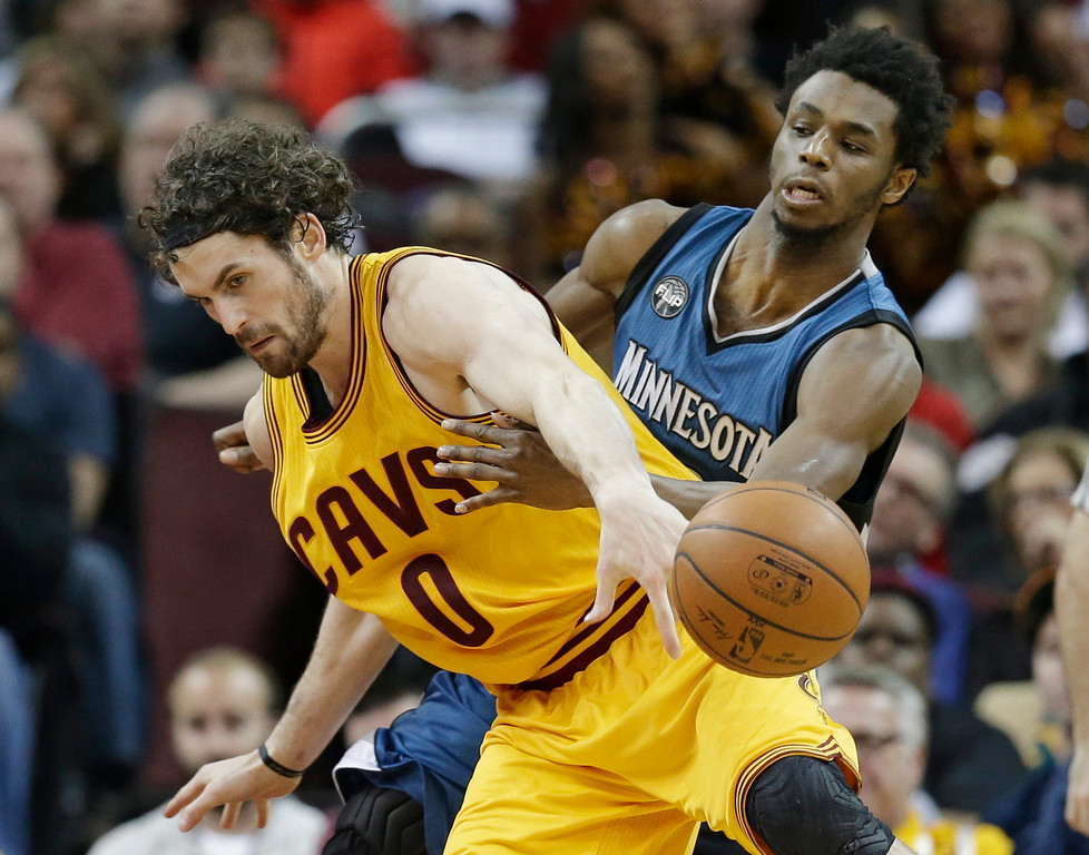 . Minnesota Timberwolves\' Andrew Wiggins, right, from Canada, knocks the ball loose from Cleveland Cavaliers\' Kevin Love in the second half of an NBA basketball game Monday, Jan. 25, 2016, in Cleveland. The Cavaliers won 114-107. (AP Photo/Tony Dejak)
