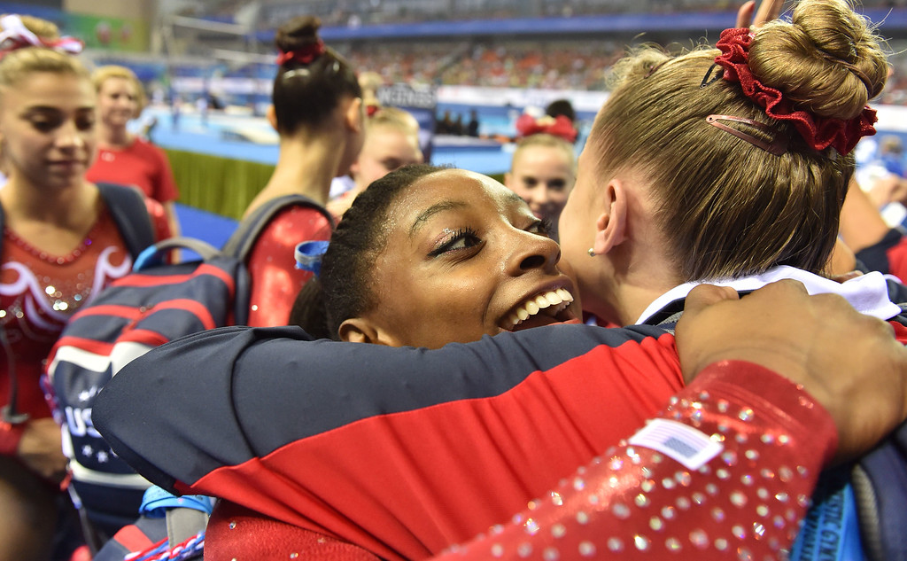 . US gymnast Simone Biles (C) celebrates the team\'s victory with teammate Madison Desch (R) during the women\'s team final of the Gymnastics World Championships in Nanning, in China\'s southern Guangxi province on October 8, 2014. KAZUHIRO NOGI/AFP/Getty Images