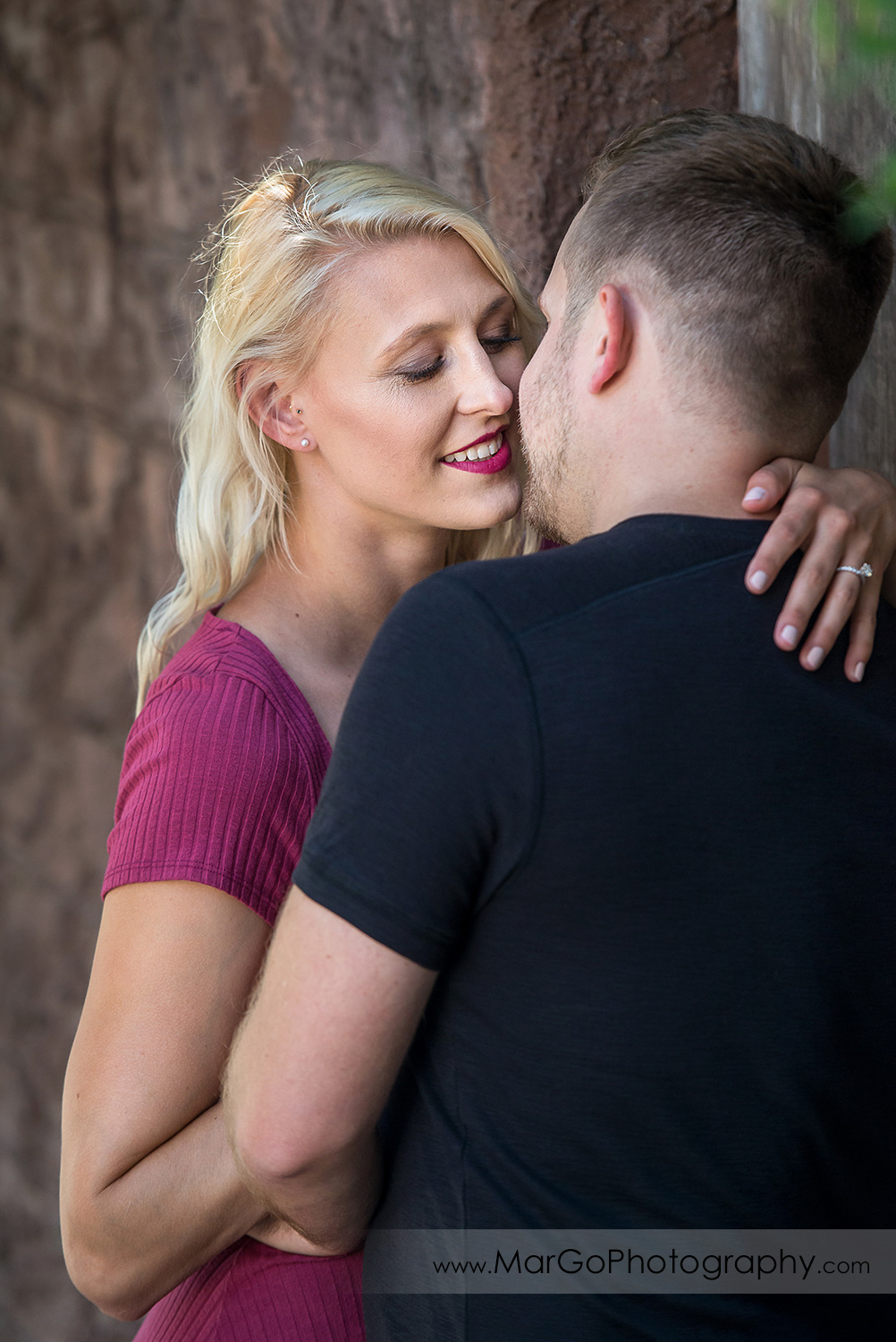 engagement session at Bernal Heights in San Francisco - portrait of woman in pink dress almost kissing man in black t-shirt