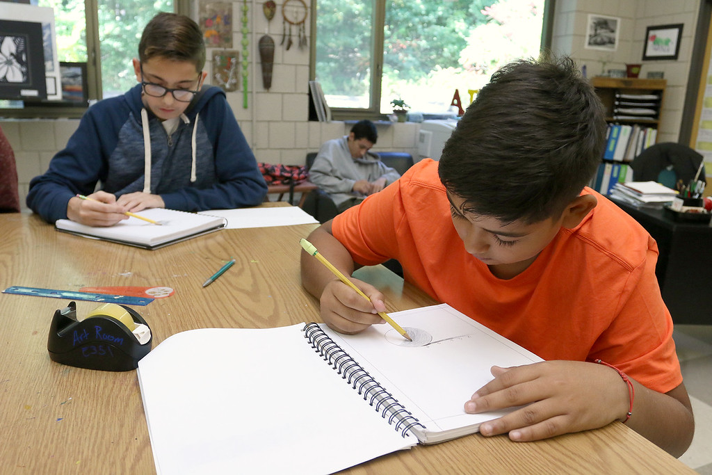 . Cristian Crespo, 14, tries to do some shading to make a circle look real in his new art class at Leominster High School on Friday, October 13, 2017. He and his brother moved to Leominster after Hurricane Maria destroyed their town in Puerto Rico. SENTINEL & ENTERPRISE/JOHN LOVE