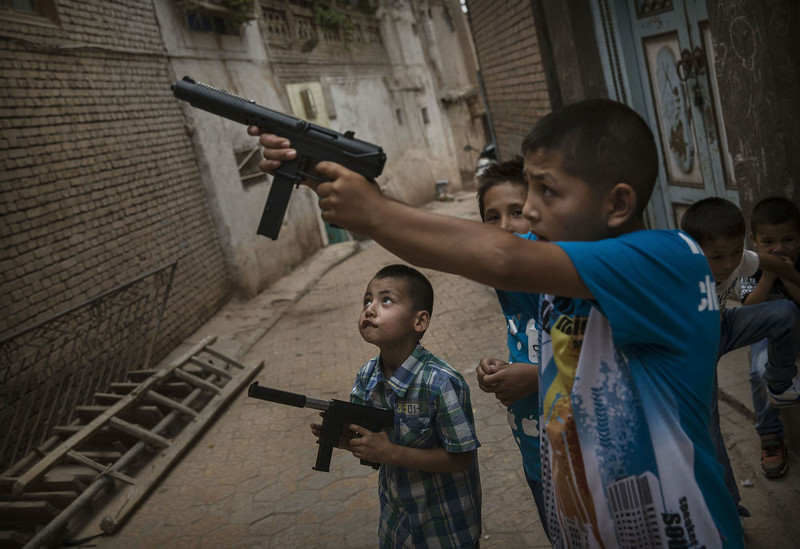 . KASHGAR, CHINA - JULY 29:  Uyghur boys play with toy guns on the Eid holiday on July 29, 2014 in alleyway in old Kashgar, Xinjiang Province, China. Nearly 100 people have been killed in unrest in the restive Xinjiang Province in the last week in what authorities say is terrorism but advocacy groups claim is a result of a government crackdown to silence opposition to its policies. China\'s Muslim Uyghur ethnic group faces cultural and religious restrictions by the Chinese government. Beijing says it is investing heavily in the Xinjiang region but Uyghurs are increasingly dissatisfied with the influx of Han Chinese and uneven economic development.  (Photo by Kevin Frayer/Getty Images)