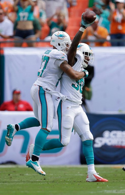 . Miami Dolphins strong safety Chris Clemons (30) is congratulated by Miami Dolphins safety Jimmy Wilson (27) after Clemons intercepted the ball during the first half of an NFL football game against the Buffalo Bills, Sunday, Oct. 20, 2013, in Miami Gardens, Fla. (AP Photo/Wilfredo Lee)