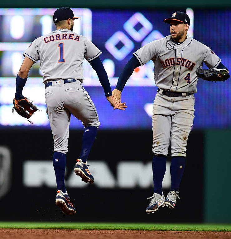 . Houston Astros\' George Springer, right, and Carlos Correa celebrate after the Astros defeated the Cleveland Indians 11-2 in a baseball game Friday, May 25, 2018, in Cleveland. (AP Photo/David Dermer)