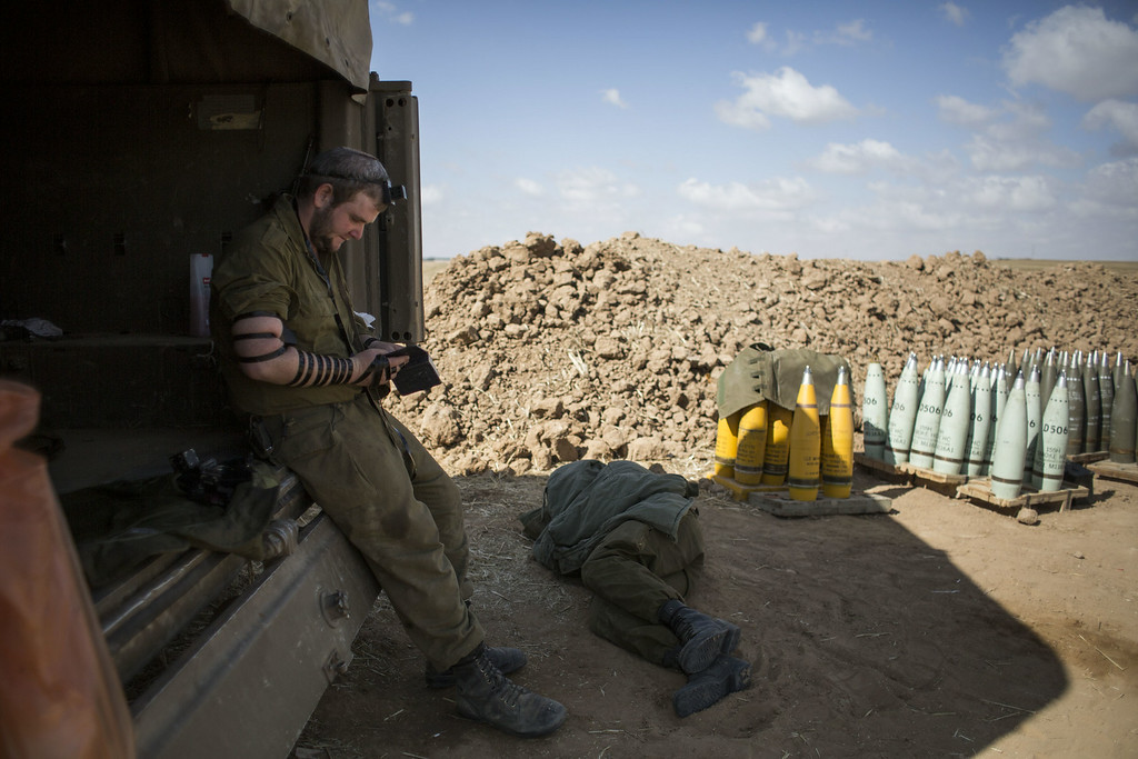 """. Israeli soldier seen praying by artillery cannon on July 16, 2014 at the Israeli-Gaza border. An Egyptian ceasefire proposal was yesterday refused by Hamas, who continued their missile bombardment on Israel. Israel has today issued a warning to 100,00 residents of northern Gaza to evacuate their homes as it continues with planned airstrikes as part of operation \'Protective Edge\'. Israeli Prime Minister Benjamin Netanyahu said he had \""""no choice\"""" but to intensify the military operation in light of the refusal to ceasefire terms from Hamas officials. (Photo by Ilia Yefimovich/Getty Images)"""