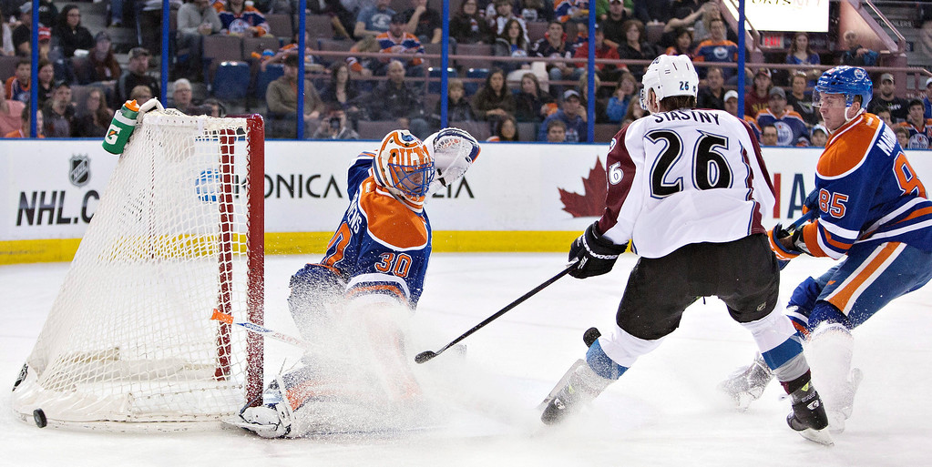 . Colorado Avalanche\'s Paul Stastny (26) is stopped by Edmonton Oilers goalie Ben Scrivens (30) as Martin Marincin (85) defends during first period NHL hockey action in Edmonton, Alberta, on Tuesday April 8, 2014. (AP Photo/The Canadian Press, Jason Franson)