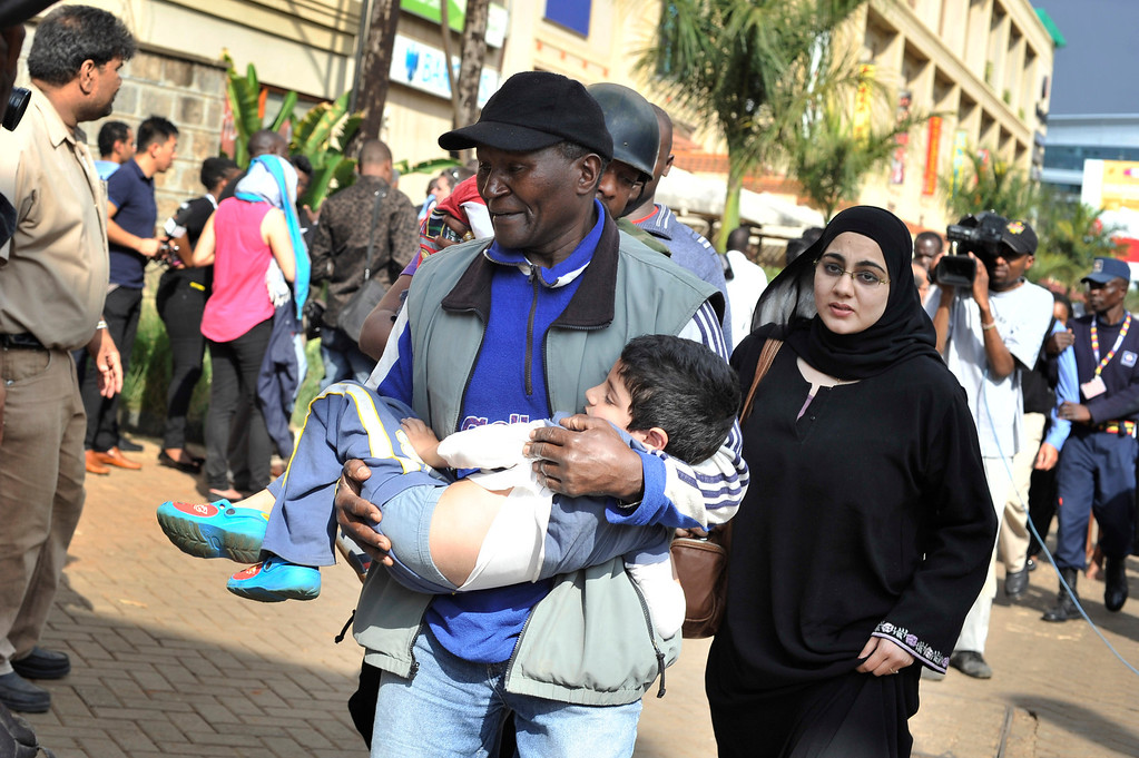 . A rescue worker helps a child outside the Westgate Mall in Nairobi, Kenya Saturday, Sept. 21, 2013, after gunmen threw grenades and opened fire during an attack that left multiple dead and dozens wounded.  (AP Photo/Riccardo Gangale)