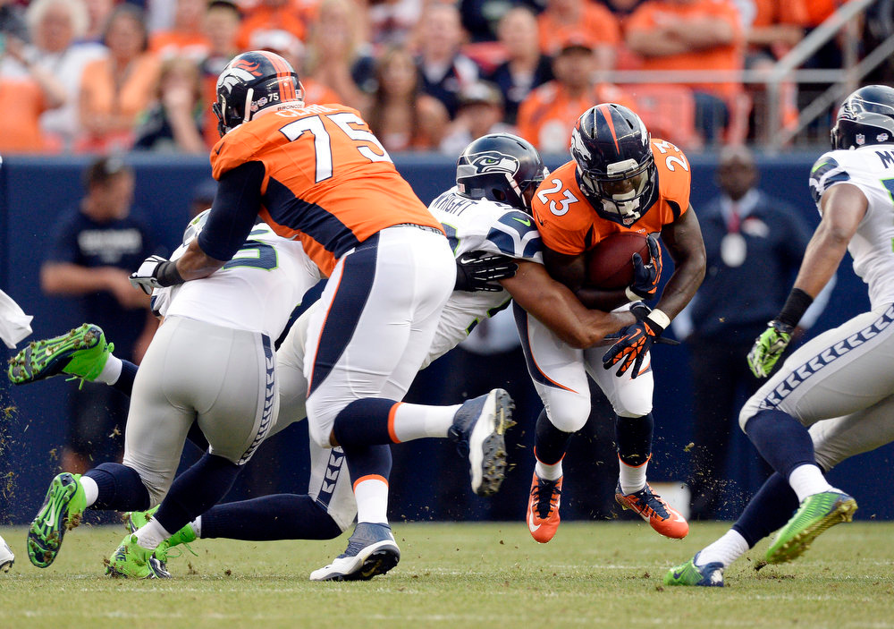 . Running back Ronnie Hillman (23) of the Denver Broncos gets taken down by outside linebacker K.J. Wright (50) of the Seattle Seahawks during the first quarter.  The Denver Broncos vs the Seattle Seahawks At Sports Authority Field at Mile High. (Photo by John Leyba/The Denver Post)